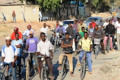 Cyclists waiting at a level crossing - On the train from Mwanza to Dar Es Salaam, Tanzania.