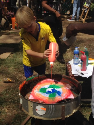 Leon adding the finishing touches to his spin art painting at the Nairobi Art Centre