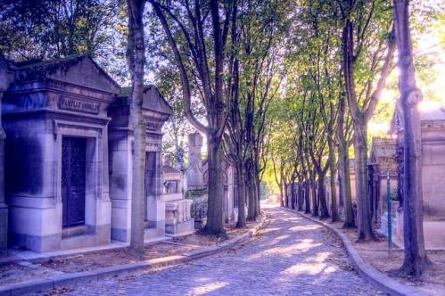 Tree-lined cobblestone paths in Père Lachaise Cemetery, Paris, France